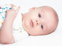 Baby lying on white sheet Stock Photography