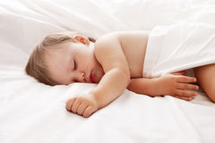Baby lying in white sheets stock photos