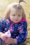 Baby Mädchen getränk sitting Flasche Park lizenzfreies stockbild