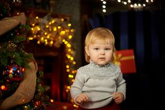 Baby in a magical setting sits on the background of a fireplace royalty free stock image
