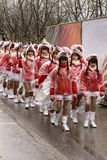 Baby majorettes marching wrapped up against rain at Carnival parade Stock Image