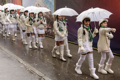 Baby majorettes under umbrellas against rain at Carnival parade,. STUTTGART, GERMANY - FEBRUARY 09: a group of baby majorettes in parade stay under umbrellas Stock Photography