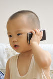Baby make a call. A chinese cute baby is making a call by the mobile phone Royalty Free Stock Photo
