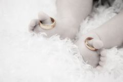 ...and Baby Makes Three. B&W image of baby feet with the big toes each holding a wedding band Stock Image