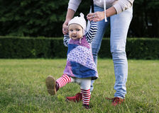 A baby is making the first steps. Cute baby in the hat is making the first steps with the mother Stock Photography