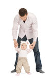 Baby making first steps with father help. Picture of baby making first steps with father help stock photos