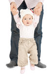 Baby making first steps with father help. Picture of baby making first steps with father help royalty free stock photos