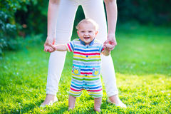 Baby making his first steps. Cute funny happy baby in a colorful shirt making his first steps on a green lawn in a sunny summer garden, mother holding his hands Royalty Free Stock Image
