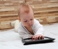 Baby making notes on his tablet PC Stock Photos