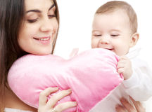 Baby and mama with heart-shaped pillow stock images