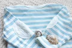 Baby marine theme 2. Striped white and blue baby top on cotton knit background, with shells stock image