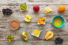 Baby mash food. Raw fruits next to puree. Top view Stock Images