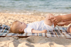 Baby massage on the beach. Stock Photos