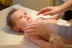 Baby massage. Massagist making massage to a small baby. stock image