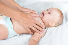 Baby massage. Mother massaging infant belly Royalty Free Stock Photography