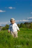 Baby on meadow. Blue sky and green grass Stock Image