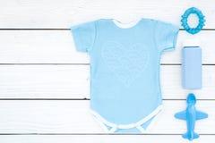 Baby med hjärtfelkläder för pys Bodysuit leksaker, skönhetsmedel på vitt träutrymme för kopia för bästa sikt för bakgrund royaltyfri foto