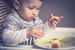 Baby with messy face eating cheese cakes Royalty Free Stock Photos