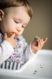Baby with messy face eats and puts finger in his mouth Royalty Free Stock Images