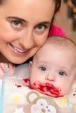 Baby met bieten op zijn mond Stock Afbeeldingen