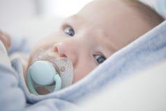 Baby met blauwe fopspeen Stock Foto