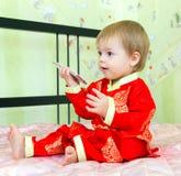 Baby met celtelefoon in feestelijke kostuumzitting op het bed Stock Foto's