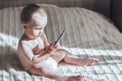 Baby met de telefoonzitting op bed Stock Foto