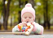 Baby met een stuk speelgoed Stock Afbeeldingen