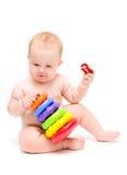 Baby met een stuk speelgoed en fopspeen Stock Foto