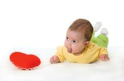 Baby met een zacht stuk speelgoed in de vorm van hart Stock Afbeelding