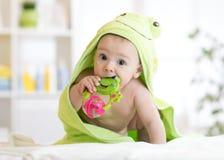 Baby met groene handdoek na het bad het bijten stuk speelgoed stock fotografie