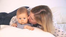 Baby met grote blauwe ogen en blond haar in bed geknuffel met mamma stock footage