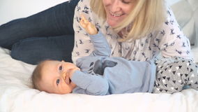 Baby met grote blauwe ogen en blond haar in bed geknuffel met mamma stock videobeelden