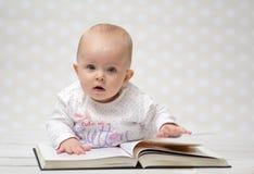 Baby met het boek Stock Foto's
