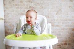 Baby met lepel op de stoel in de eetkamer, het Glimlachen en het gelukkige kind Achtergrond met exemplaarruimte Gelukkige kinderj stock foto's