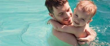 Baby met papa die in de pool zwemmen Stock Afbeeldingen