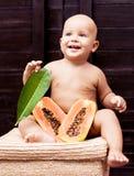 Baby met papaja stock foto's