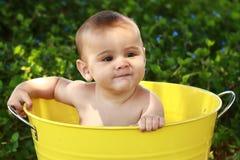 Baby met schelmse grijns in gele ton stock foto's