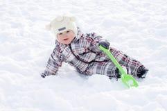 Baby met schop die in sneeuw in de winter liggen Stock Foto's