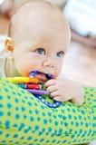 Baby met stuk speelgoed in mond Stock Fotografie