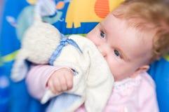 Baby met zacht stuk speelgoed Stock Foto