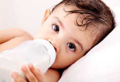 Baby milk. Baby drinking milk of her bottle. White background stock images