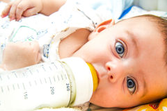 Baby and milk bottle stock image