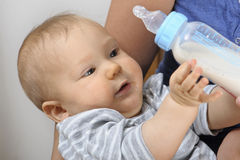 Baby with milk bottle Stock Images