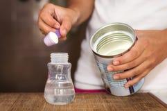Baby milk formula. Mother prepares baby milk formula Royalty Free Stock Photo