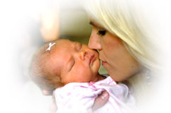 Baby Mine. Beautiful young mom softly kisses her infants cheek.  Baby is asleep and has a tiny white bow in her hair Stock Photo