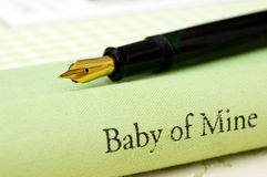 Baby of mine book pen. Close up of Baby of mine book and a pen Royalty Free Stock Image
