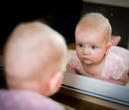 Baby with mirror. Baby girl with a mirror Royalty Free Stock Image