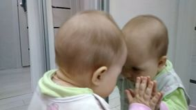 Baby and mirror. The baby rejoices at his image in the mirror and kisses him stock video footage