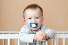 Baby mit Attrappe im weißen Bett Stockfotos